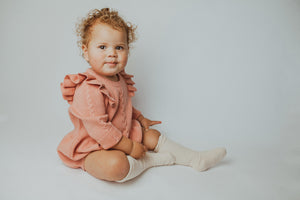 Baby girl wearing our pink cable knit romoer. Beautifully stylish, warm and cosy to keep your little girl warm. Long sleeves, frill shoulders pink romper is just divine.