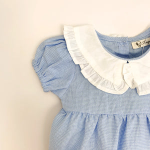 Detail shot of one of our beautiful baby girls rompers. Puff sleeves and a frill collar add so much style to this little garment. Perfect outfit for girls in 100% cotton.