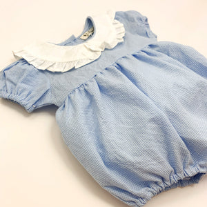 Toddler and baby girls romper made in 100% cotton fabric, short sleeves and a frill collar in a blue gingham print. Cute summer rompers for girls at Bel Bambini baby boutique.