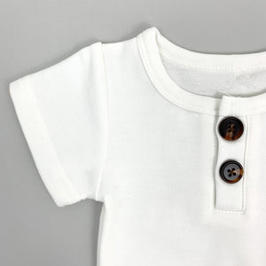 Boys summer outfit. Detail shot of our baby boys tshirt, featuring two buttons to the centre front neckline. Short sleeve tee with matching shorts for baby boys and toddler boys. Shop our baby clothing at Bel Bambini baby boutique.