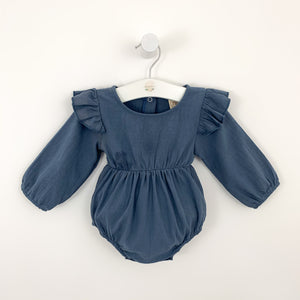 Baby girls romper with pretty flutter shoulder details, a beautiful outfit that can be dressed up or down with layers for any season. Long sleeves in a lightweight fabric.