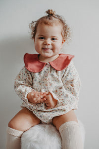 Baby modelling our spting romper in a beautiful floral print with a contrast statement collar.