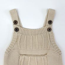 Load image into Gallery viewer, Baby boys knitted romper in 0-18 months. Beautiful latte shade made from cotton yarn so its supersoft and comfortable against your little ones skin. Two button fastenings to the shoulder straps to allow for an adjustable length and growing room.