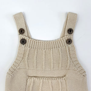 Baby boys knitted romper in 0-18 months. Beautiful latte shade made from cotton yarn so its supersoft and comfortable against your little ones skin. Two button fastenings to the shoulder straps to allow for an adjustable length and growing room.
