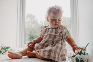 Baby girls romper dress in a neutral tartan print, Aun=tumnal hues and classic style make this girls romper dress extra special. Beautiful and super stylish. Team with rib knit tights from our collection of baby and toddler accessories.