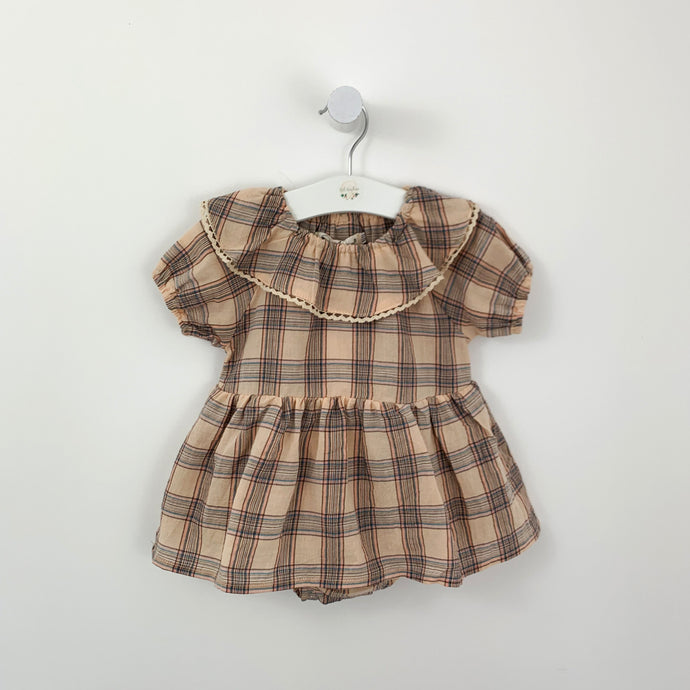 Baby girl romper dress in tartan. Neutral base with hues of pink and blue and a beautiful trim to the collar. Puff sleeves and a floaty A-line skirt to finish the overall stylish look.