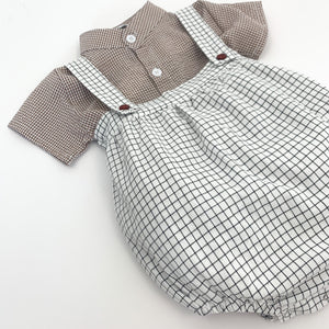 Our plaid romper with a matching hat and a gingham printed shirt. Natural colourway but also available in grey. 0-6 months, 6-9 months, 9-12 months, 12-18 months boys clothing at Bel Bambini baby boutique.