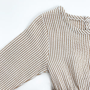 Detail showing our baby girls stripe print romper in neutral. Textured fabric base and long sleeves. Perfect to layer up for the colder days. Autumn, winter romper.