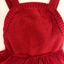 Load image into Gallery viewer, Detail shot of the knitted heart featured on our red knitted romper for baby and toddler girls, 0-2 years. Christmas romper in red for girls is warm, soft and comfortable.