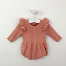 Load image into Gallery viewer, Infanyt knitted romper with cable knit detailing and flutter shoulders. This is super warm and comfortable for baby and toddler girls. Available in rose pink. The flutter shoulders make this knitted romper super stylish. Long sleeves and button fastenings to the crotch. Available for baby girls up to 2 years.