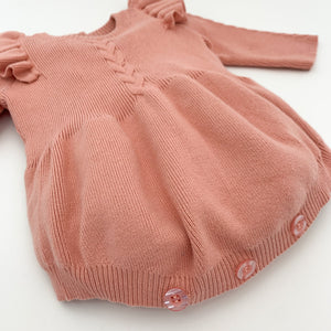 Cable knit romper for baby girls aged 0-2 years. Available in Rose Pink this romper is warm and cosy with a really soft handfeel. Long sleeves for extra warmth too. Shop our baby and toddler collections online at Bel Bambini baby boutique.