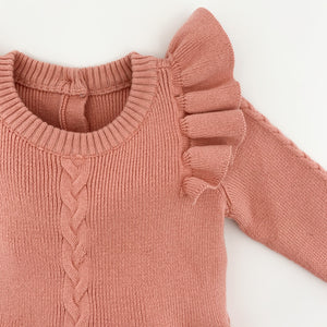 Our cable knit romper in rose pink has beautiful flutter shoulder details, long sleeves and button fastenings to the crotch. Beautiful knitted styles for infants and toddlers at Bel Bambini baby boutique.