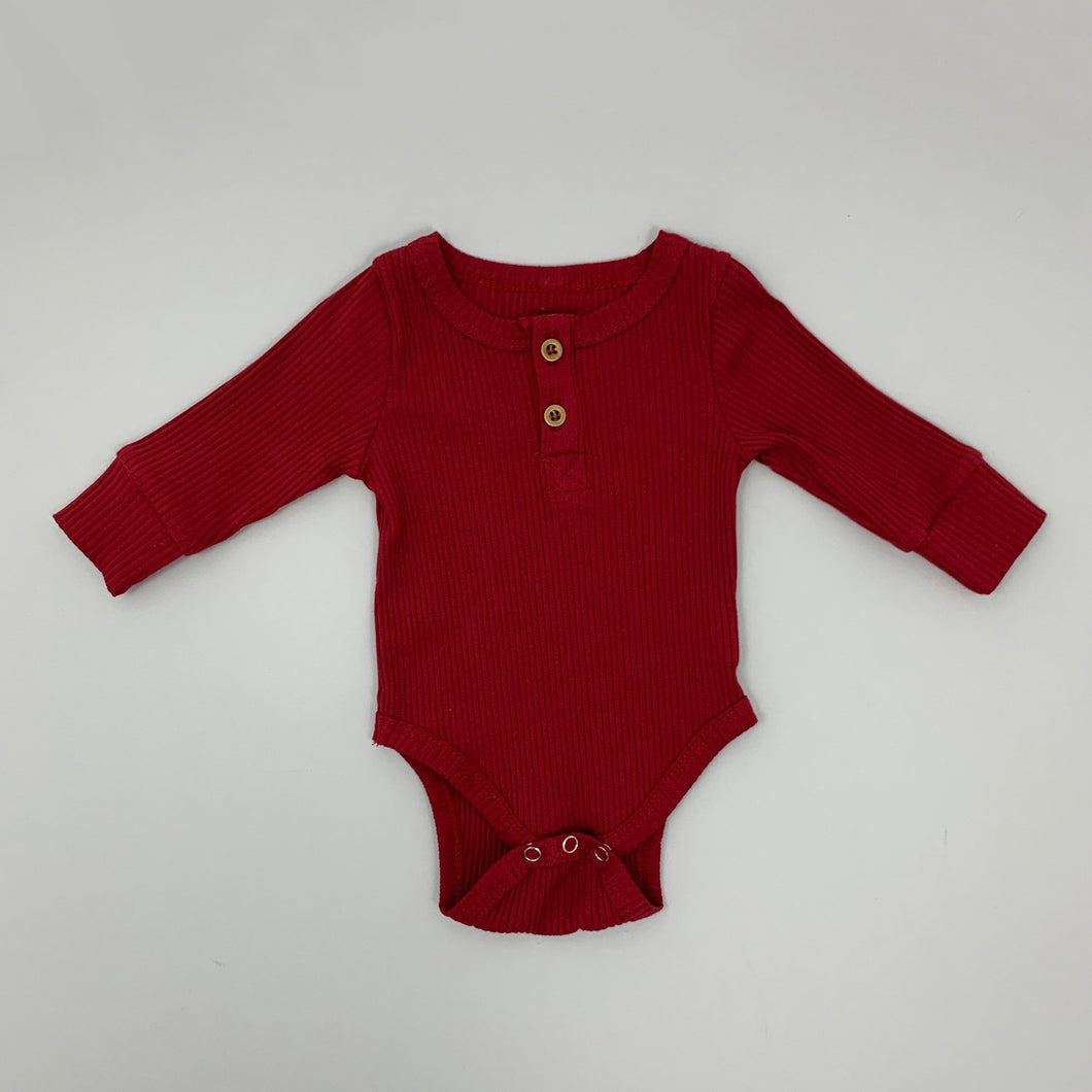 Baby Ribbed vest in both berry and latte, two buttons to the top neckline with a round neck. Long sleeved layering essential vest for babies and toddlers. Popper fastenings at the bottom.