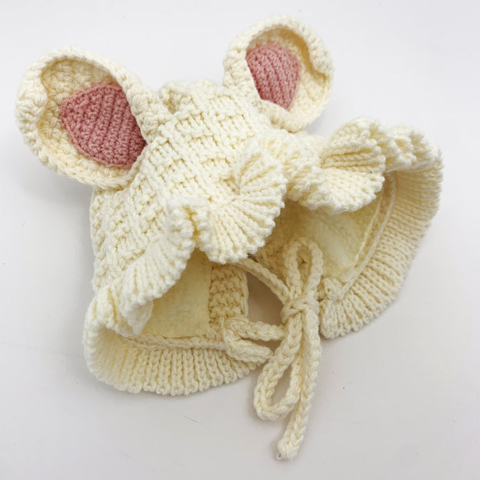 Cream knitted hat for baby girls aged 6-24 months. Bunny ears and a pretty frill are just adorable. Warm and cosy knitted hat perfect for winter.