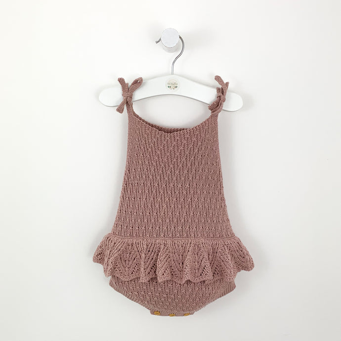 baby girls knitted romper in dusty pink with a scalloped frill arounf the hip to make it extra pretty. Shoulder ties into a bow and button fastenings to the bottom. Beautiful baby and toddler clothing at Bel Bambini.