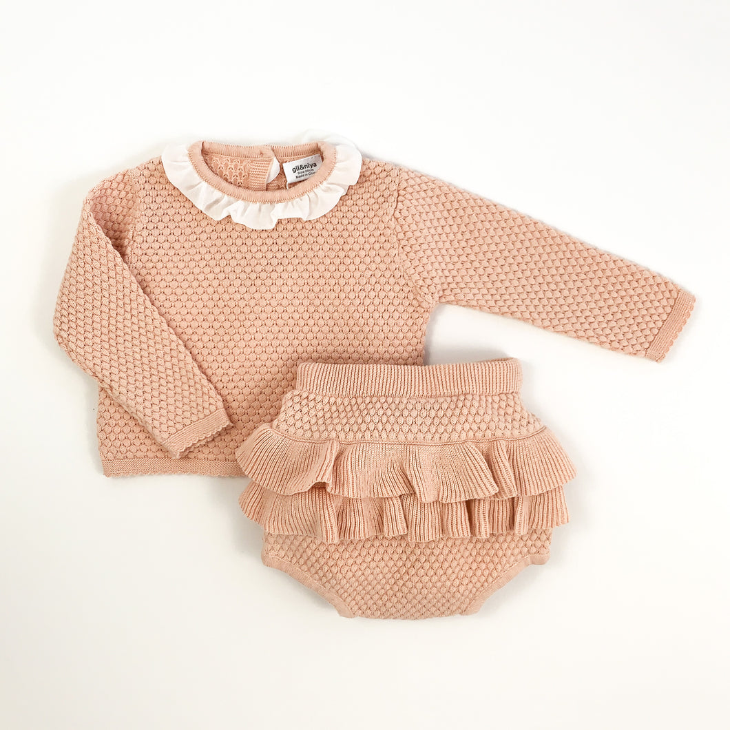 baby and toddler cute knitted set in soft shell pink. Adorable bloomers and knitted top for girls. Top has a pretty contrast frill to the neck in white and button fastenings down the back. Long sleeves. Stunning baby girl outfit.
