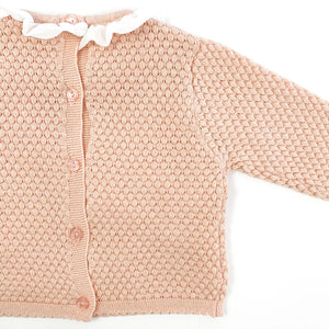 Detail shot of our Bel Bambini two piece knitted set in shell pink. Stunning girls knitted outfit. button fastenings doen tge centre back and a frill collar, such a beautiful baby set. 0-24 months baby clothing and toddler styles.