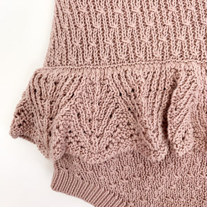 Photo showing a detail shot of our baby girls knitted romper in dusty pink. The scalloped frill to the hips make this such a beautiful style. Shop our romper collection online.