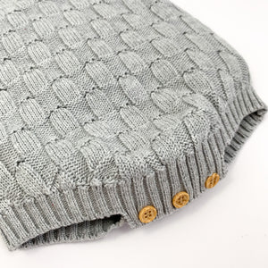 Grey weave knit romper made from cotton yarn for baby boys 0-18 months. Image showing three button fastenings to the bottom of the romper and the beautiful knitted detailing. Shop baby boys clothing at Bel Bambini baby boutique.