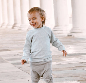 Boys sweater in grey marl. High neck sweater for boys in a beautiful thick and warm fabrication, long sleeved high neck sweater in grey marl. Sizes 0-2 years.