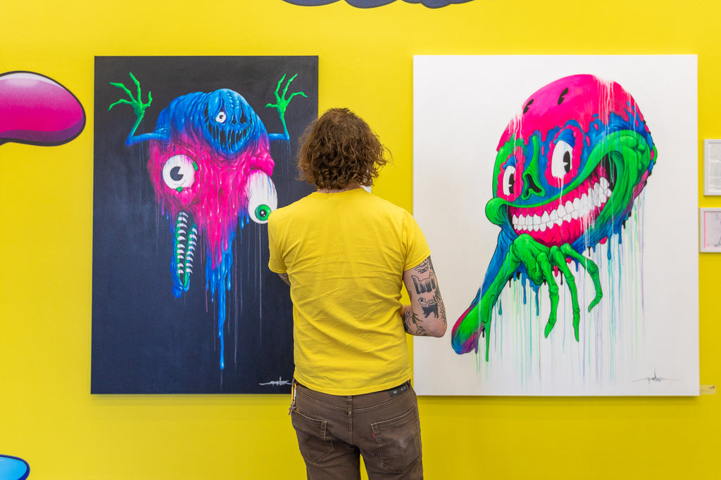 A gallery visitor viewing Alex Pardee artwork