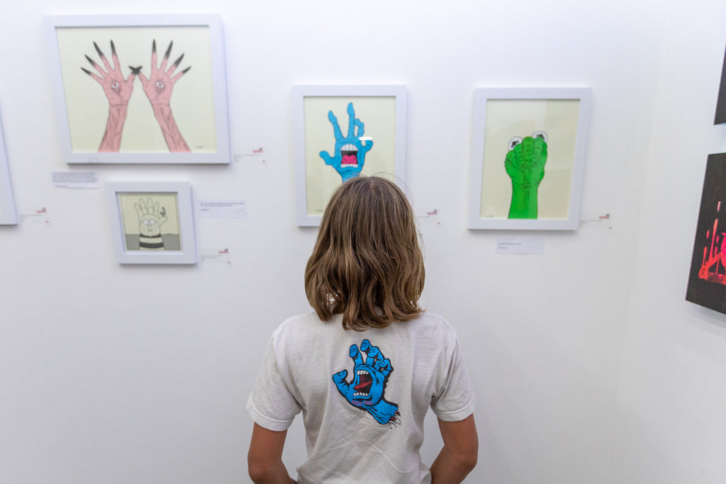 A gallery visitor looking at Alex Pardee artwork