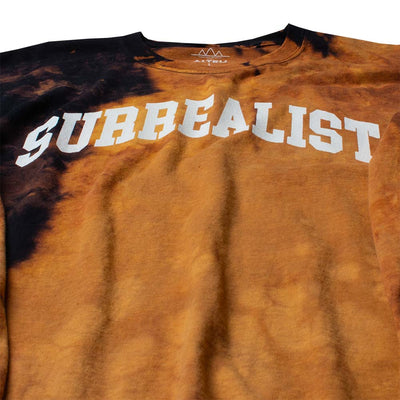 "Close up of Long Sleeve Men's Tee with ""SURREALIST"" printed on the chest of black shirt that has been bleached for effect."