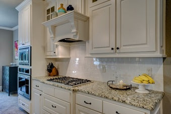 A kitchen with a granite countertop and white cabinetry