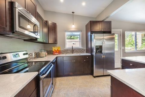 A kitchen with concealed cabinets and white quartz countertops