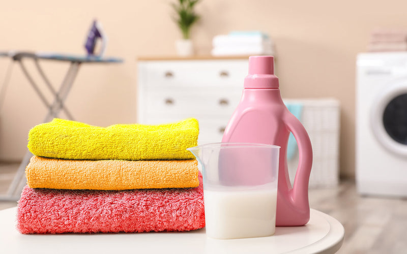 folded yellow, orange, and pink towels and a small amount of a detergent with the detergent bottle on the table while an ironing table, a dresser and a washing machine are appearing behind them