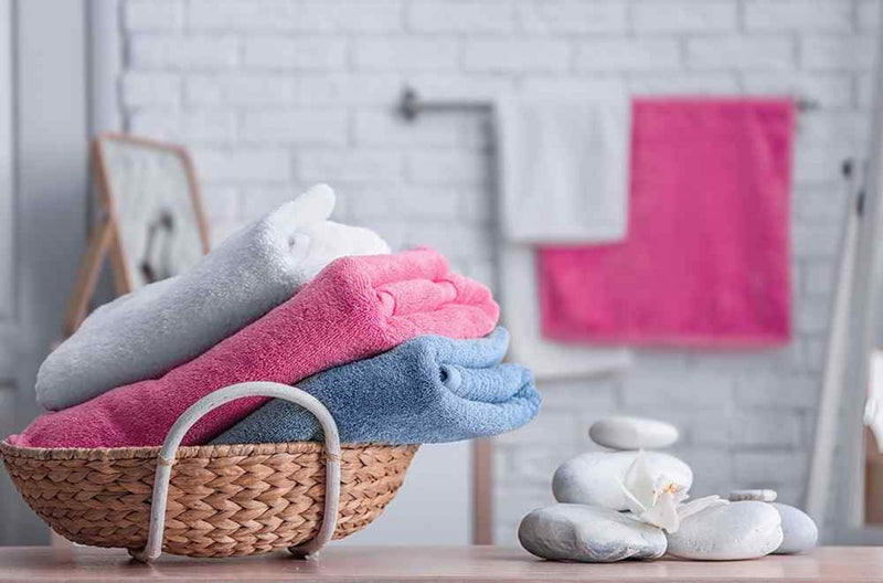 towels in a basket in bathroom and the little rocks near the basket, hanged towel, what is a turkish towel
