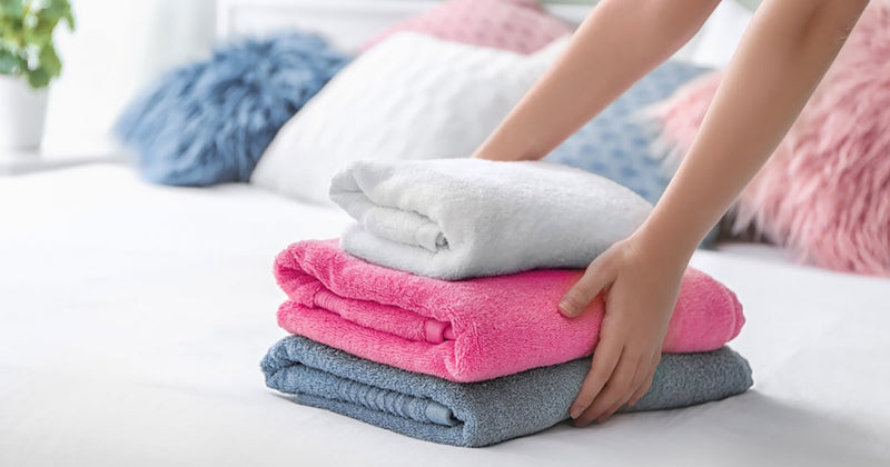 woman holds terry cloth towels standing on the bed