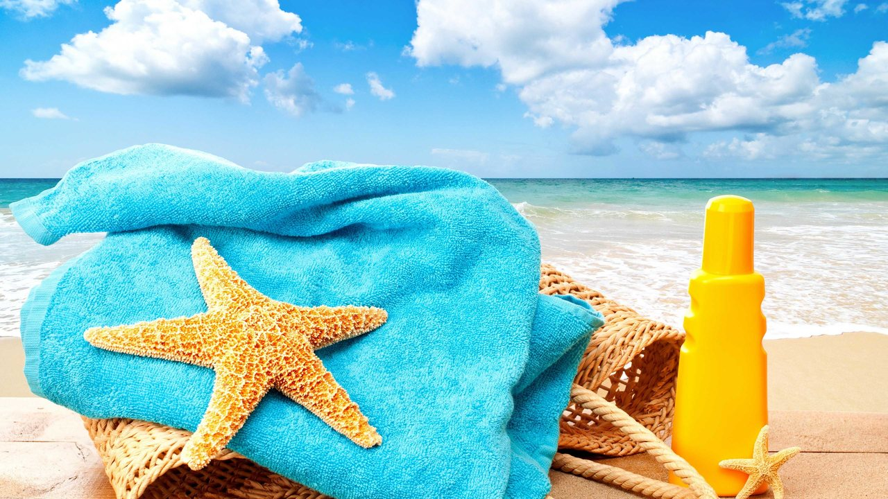 beach towel, towel, starfish and sunscreen on the beac