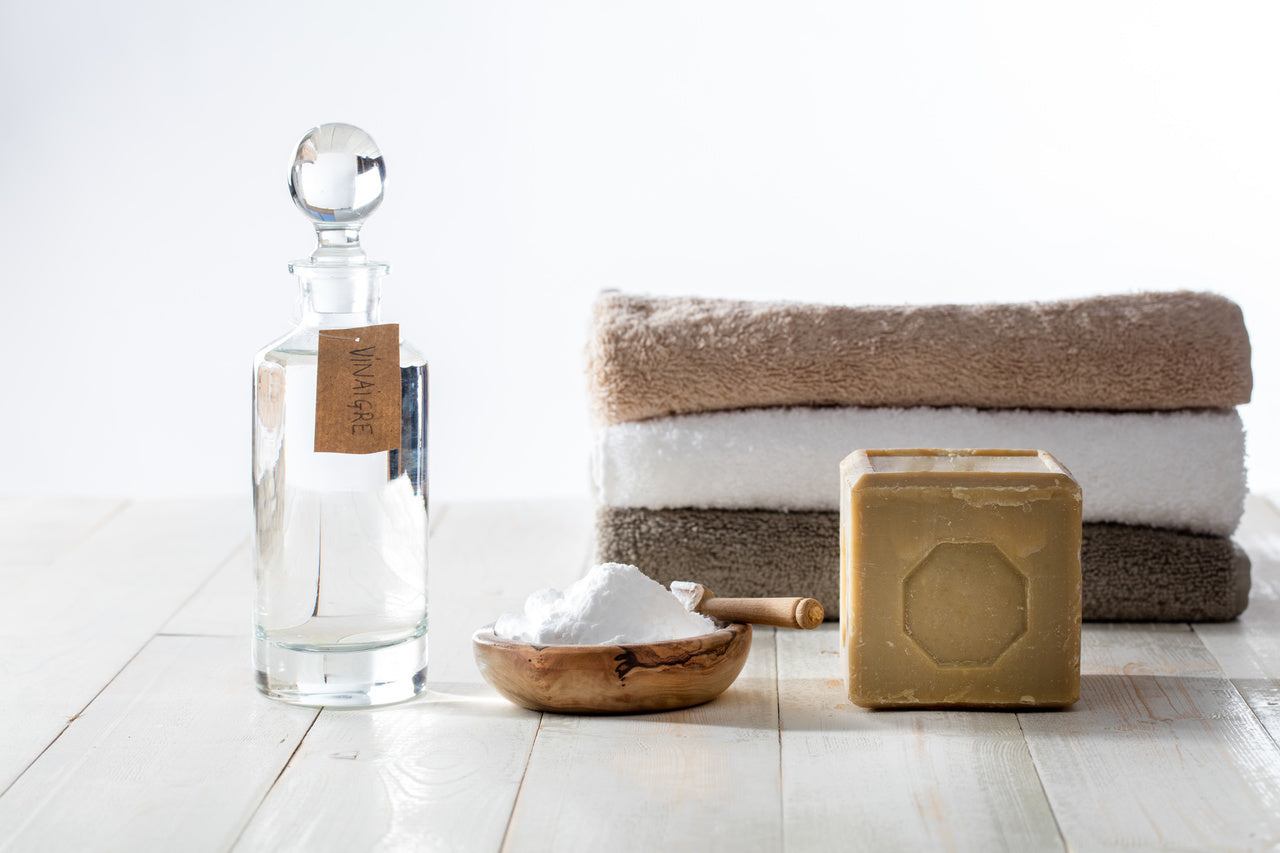 a vinegar, natural soap, carbonate and folded towels standing on the counter