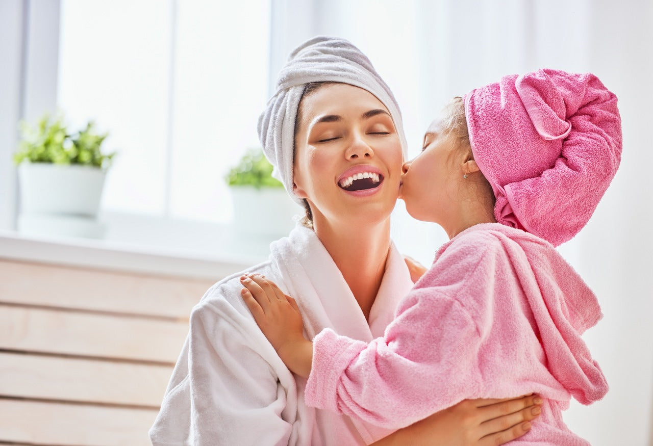 a mother wears white bathrobe and her daughter wears pink bathrobe