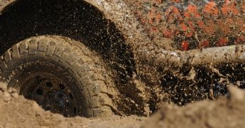 The tire of a hummer rotating at high speed deep in mud.