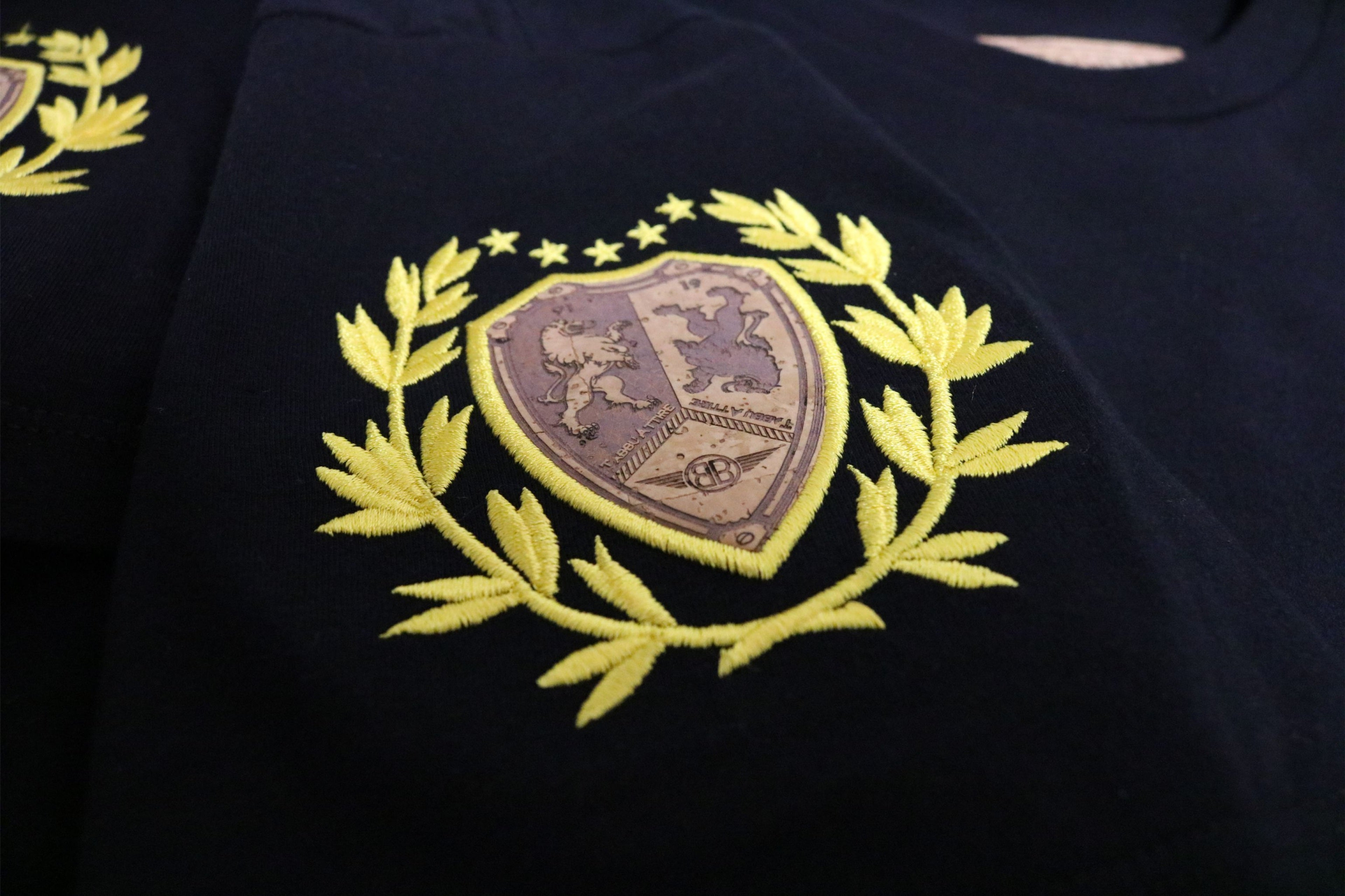 Lion Cork Shield Crewneck Tee in Black with Yellow Embroidery