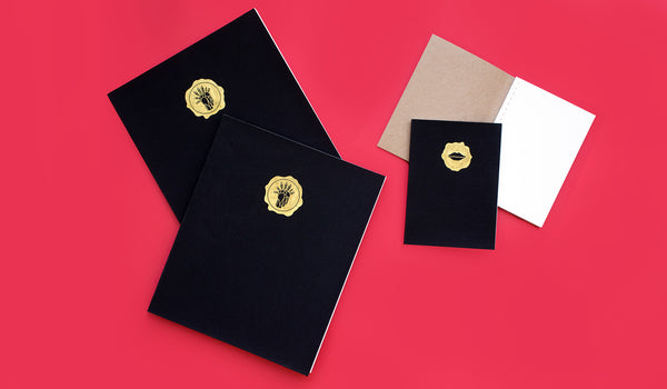 True to the designer's look of edgy refinement, these handmade, Swiss bound sketchbooks are covered in black linen and stamped in gold foil. Choose from three of Kelly's signature silhouettes for their stamped emblem; the Classic Kiss and Legs, and Head Trip. Add your monogram to the cover in gold foil to make them even more personal. Forty perforated pages of watercolor paper per book, available in three sizes.