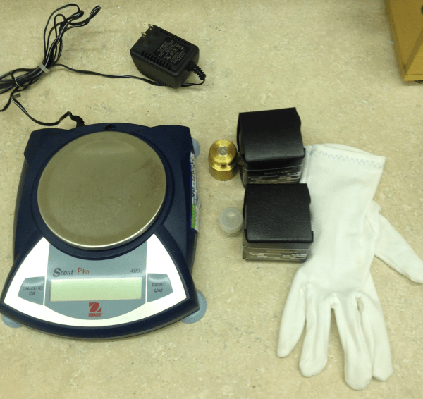 A electronic scale with calibration weights and white gloves.