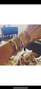 Stackable gold/silver tube bracelets.