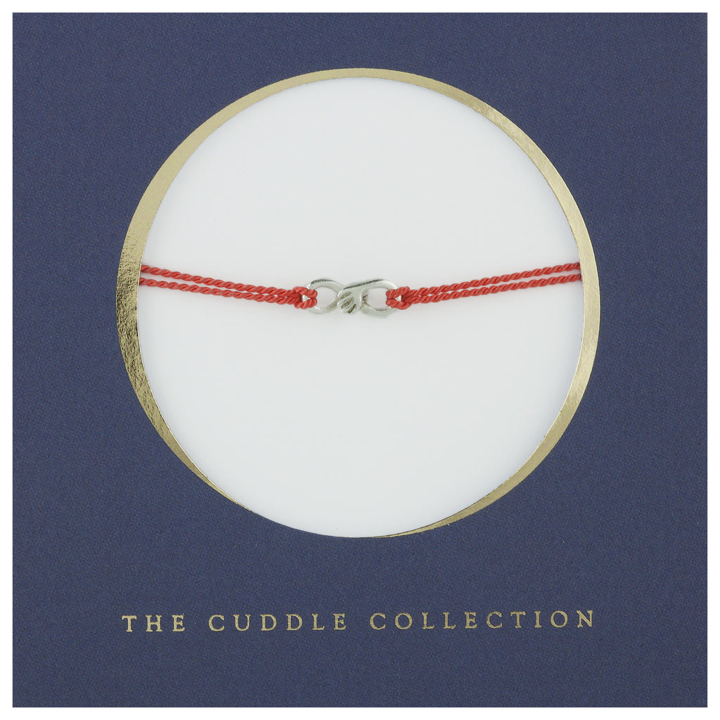 Cuddle charm bracelet on red silk thread
