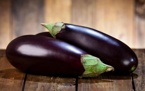 two-eggplants-on-a-wooden-table