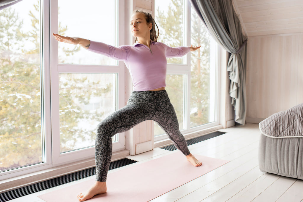 Young woman holding a yoga pose with her feet spread apart and arms spread apart in a living room. She has light skin and brown dreadlocked hair. She is concentrated and looking forward. She is wearing black patterned yoga pants and a pink long sleeve shirt.