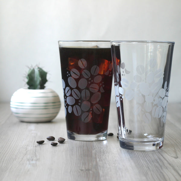 Pair of pint glasses with coffee beans etched around the outsides. One full of iced coffee.