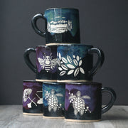 Handmade pottery mugs with dripping glaze in blue/green and purple, engraved by Bread and Badger