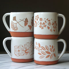 floral engraved pottery mugs with ginkgo leaves, cherry blossoms, dogwood flowers, and tea leaves