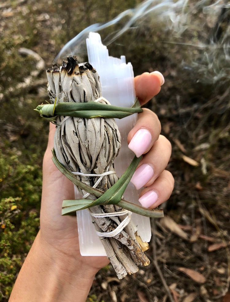 Burning sage stick wrapped with selenite crystal in nature. Smudging can clear inharmonious vibrations and restore crystals' natural energies