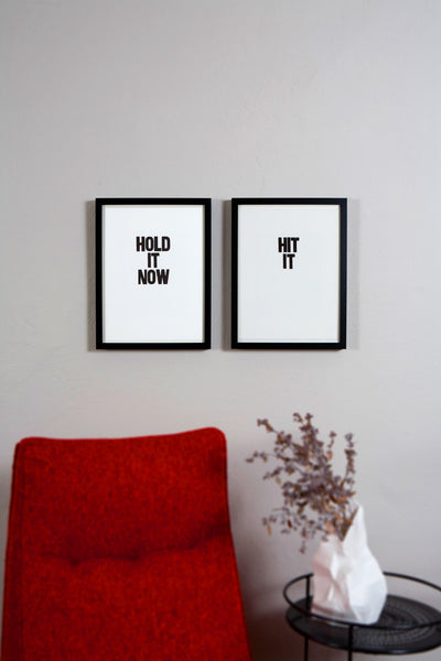 "Framed letterpress poster pair with the sayings ""Hold it now"" and ""Hit it"""