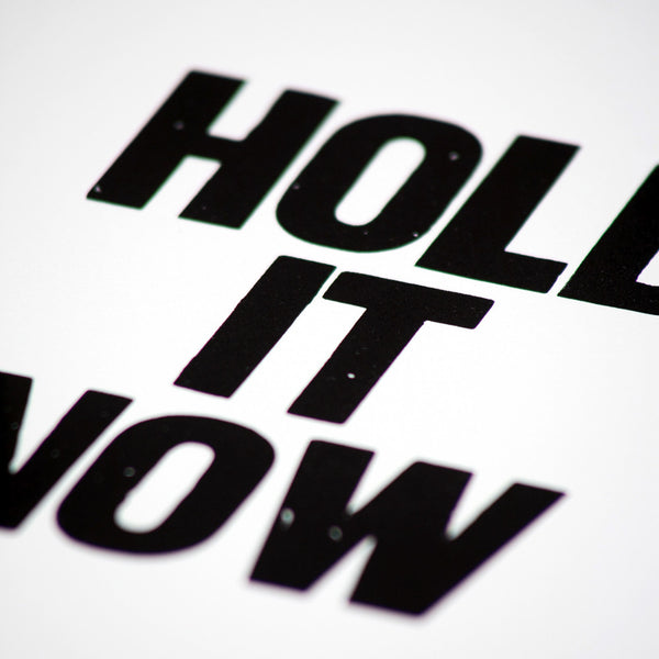 "Letterpress poster with the saying ""Hold it now"""