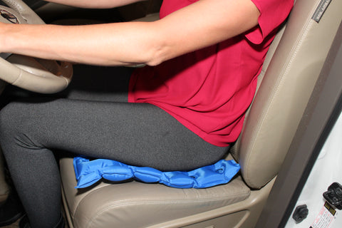 A woman with pain in her neck, back, or shoulder, pinched nerves, pressure core, bruised tailbones, sciatica, or hip pain in need of support while sitting for long periods of time  enjoying the EverRelief Inflatable Seat Cushion in the car.